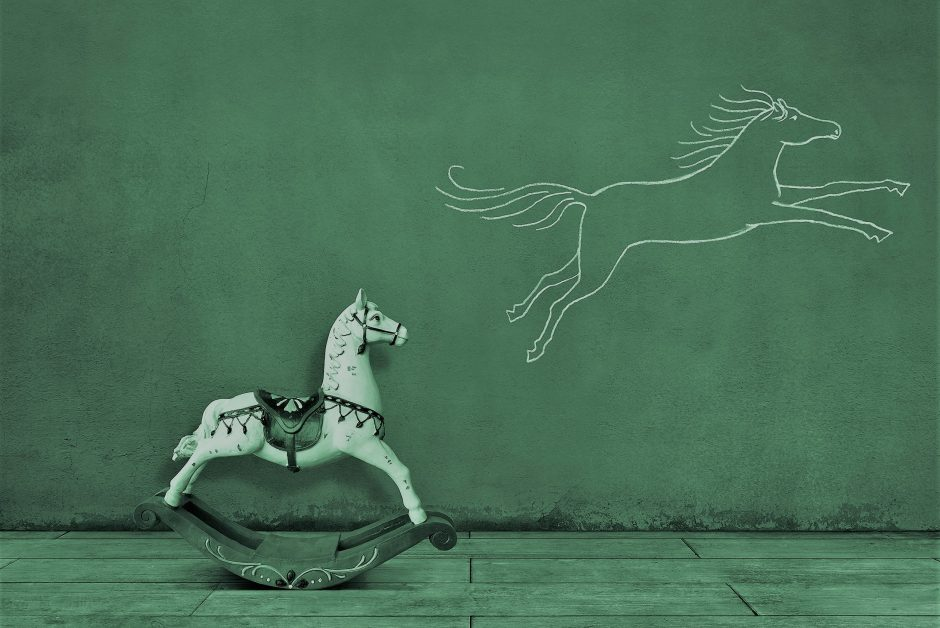 Side view of wooden rocking horse on wooden floor with running (or jumping) horse sketched (chalk drawing) on the wall.